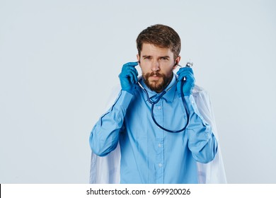 Medicine, doctor with a beard puts on a stethoscope on a light background