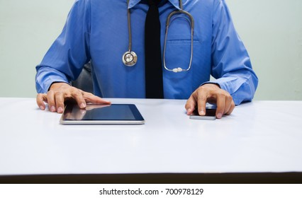 Medicine doctor in blue shirt working with digital tablet and smartphone at table  in the hospital
