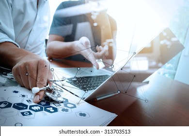 Medicine doctor hand working with modern computer and two colleagues discussing data  on wooden desk as medical concept