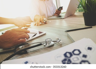 Medicine doctor hand working with modern computer and digital tablet with his team on wooden desk as medical concept