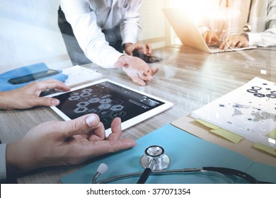 Medicine doctor hand working with modern computer and digital pro tablet with his team with graphics medical diagram on wooden desk,sun flare effect