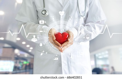 Medicine doctor holding red heart shape in hand and icon medical network connection with modern virtual screen interface, medical technology network concept