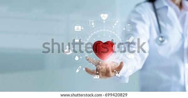 MedizinArzt, der eine rote Herzform in Hand mit einem medizinischen Icon-Netzwerk Verbindung moderne virtuelle Bildschirm-Schnittstelle, Dienst-Geist-und Medizintechnik-Netzwerk-Konzept