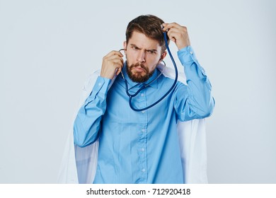 medicine, doctor a man in a white lab coat with a stethoscope on a light background