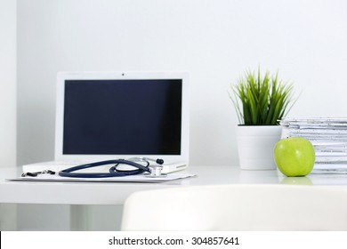 Medicine doctor's working table. Laptop, papers, green apple and stethoscope lying on table at physician's office. Healthcare and medical concept