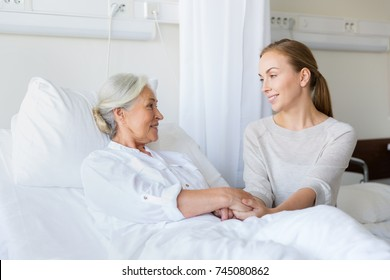 medicine, family, healthcare and people concept - daughter visiting and cheering her mother lying in bed at hospital ward