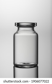 Medicine glass jar, capacity for liquid medicines with an open neck without stopper. Close up shot on a gray background.