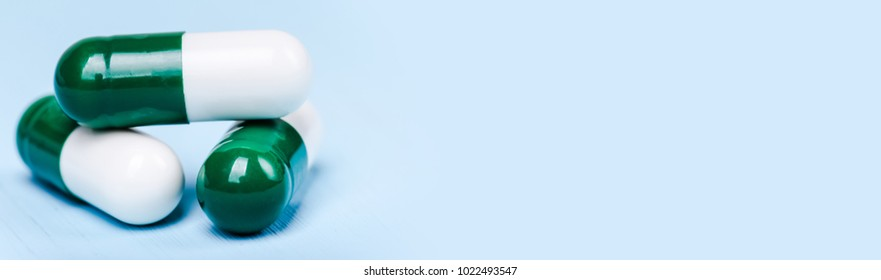 Medicine green and white pills or capsules on blue background with copy space. Drug prescription for treatment medication. Pharmaceutical medicament, cure in container for health. Antibiotic