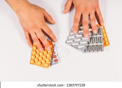 Medicine. Hands holding colorful packaging tablets on a white background. Health, vitamins.