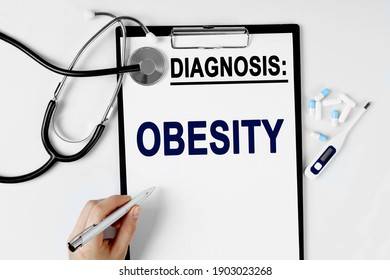 Medicine and health concept. On the table are a stethoscope, a pill thermometer, and a diagnosis sheet. The text is written on the sheet with the diagnosis - OBESITY