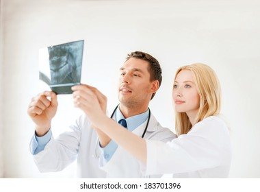 medicine and healthcare concept - smiling male doctor or dentist with nurse looking at x-ray in hospital