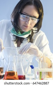 Medicine and Healthcare Concepts. Female Laboratory Staff Dealing with Flasks Filled with Chemicals During Scientific Experiment in Lab. Vertical Image Orientation