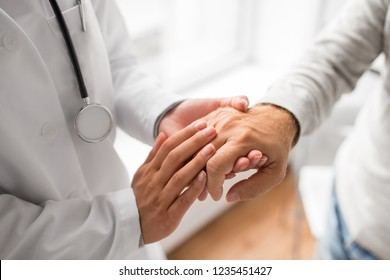 medicine, healthcare and old age concept - close up of young doctor holding senior patient hand