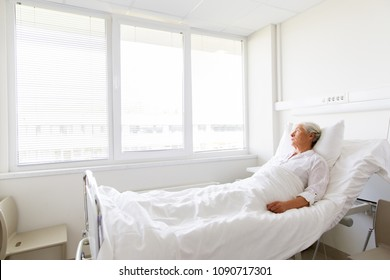 medicine, healthcare and old people concept - sad senior woman lying on bed at hospital ward