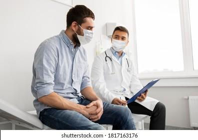 Medizin, Gesundheitsversorgung und Pandemie-Konzept - männlicher Arzt mit Gesichtsschutzmaske zum Schutz vor Viruserkrankungen mit Zwischenablage und jugendlicher Patientin im Krankenhaus