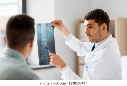 medicine, healthcare and people concept - doctor showing x-ray to patient at medical office in hospital