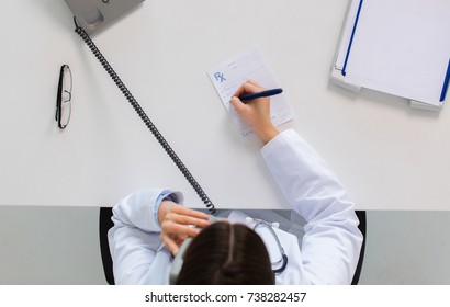 medicine, healthcare and people concept - doctor with prescription calling on phone at table in clinic
