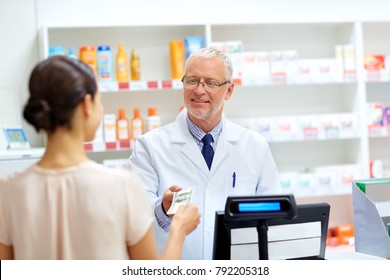 medicine, healthcare and people concept - female customer paying money to senior pharmacist at pharmacy cash register