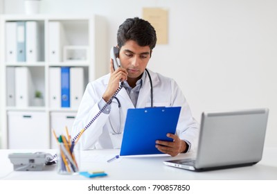 medicine, healthcare and people concept - male doctor with clipboard calling on phone at clinic