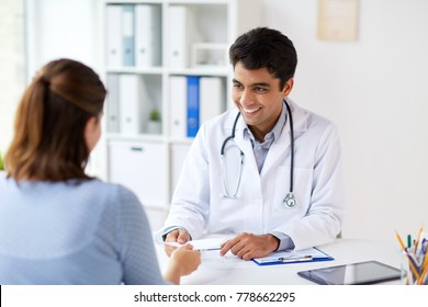 medicine, healthcare and people concept - smiling doctor giving prescription to patient at hospital