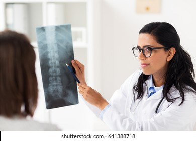 medicine, healthcare and people concept - woman patient and doctor with spine x-ray scan meeting at hospital