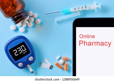 Medicine, healthcare, technology and online pharmacy concept. Top down view of pills, glucose meter, injector and tablet pc computer.
