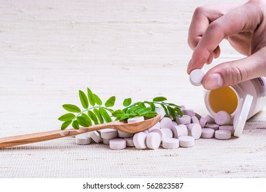 Medicine herb. Herbal pills in hand, palm, fingers with healthy medical plant. Green leaf, alternative drug. Natural pharmaceutical capsule. Vitamin supplement for care, medication