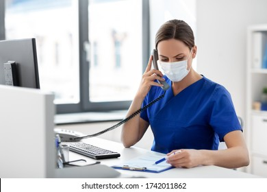 medicine, people and healthcare concept - female doctor or nurse wearing face protective medical mask for protection from virus disease with computer and clipboard calling on phone at hospital