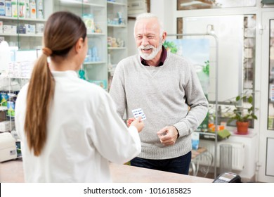 medicine, pharmaceutics, health care and people concept - happy senior man customer buying medications at drugstore