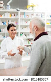 medicine, pharmaceutics, health care and people concept - happy pharmacist giving medications to senior man customer