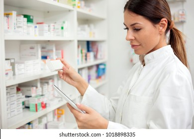 Medicine, pharmaceutics, health care and people concept - Serious young female pharmacist taking medications from the shelf.