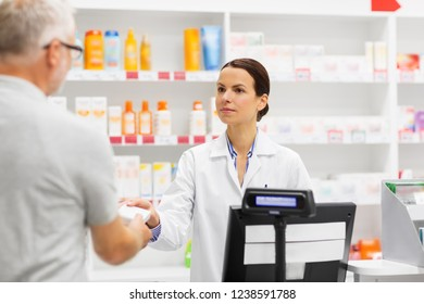 medicine, pharmaceutics, health care and people concept - apothecary and senior man customer buying drug at pharmacy