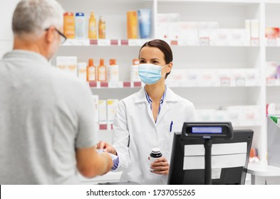 medicine, pharmaceutics, health care and people concept - apothecary wearing face protective medical mask for protection from virus disease and senior man customer buying drug at drugstore