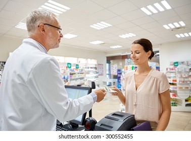 medicine, pharmaceutics, health care and people concept - smiling woman with wallet giving money to senior man pharmacist at drugstore cash register
