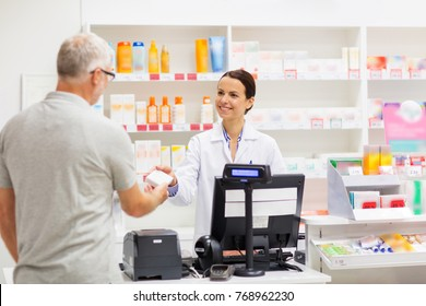 medicine, pharmaceutics, health care and people concept - apothecary and senior man customer buying drug at drugstore