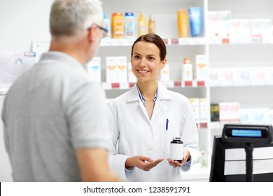 medicine, pharmaceutics, healthcare and people concept - apothecary showing drug to senior male customer at drugstore