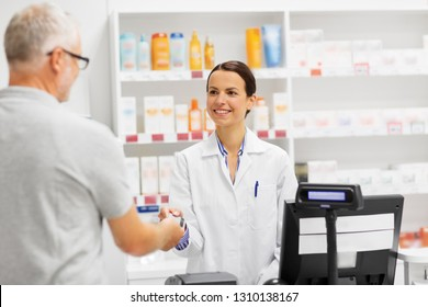 medicine, pharmaceutics, healthcare and people concept - happy smiling female apothecary taking senior customer credit card at pharmacy cash register