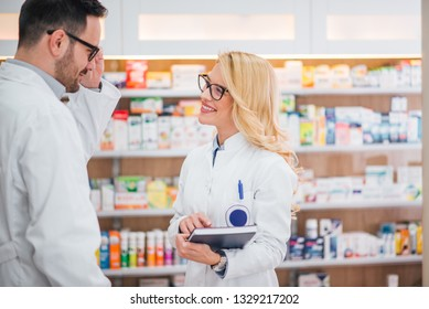 Medicine, pharmaceutics, healthcare and people concept. Two pharmacist in a drugstore.
