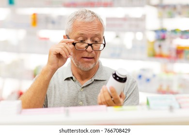 medicine, pharmaceutics, healthcare and people concept - senior male customer with drug at pharmacy