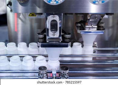 medicine pill capsules are filling in the white plastic bottle on production line machine conveyor at the medical factory.
