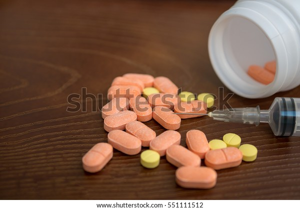 medicine pill with and syringe on wood background.