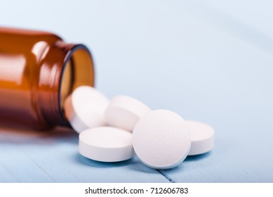 Medicine pills or capsules in bottle on white background. Drug prescription for treatment medication. Pharmaceutical medicament, cure in container for health. Antibiotic, painkiller closeup.