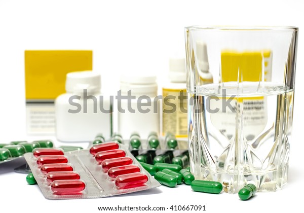 Medicine pills or capsules with glass of water on white background. Drug prescription for treatment medication. Pharmaceutical medicament, cure in container for health.