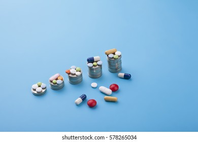 Medicine pills and coins on a blue background