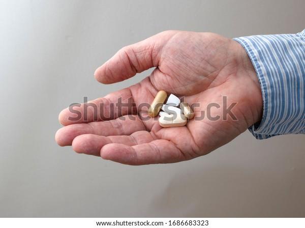 Medicine pills on adult man palm
