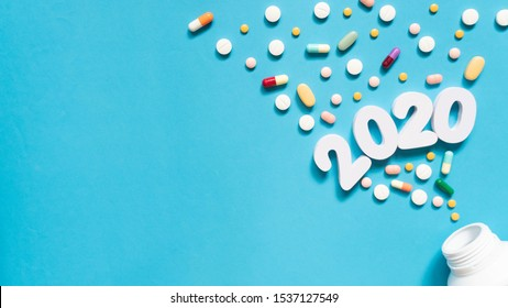 Medicine pills and white bottle w/ 2020 number on light blue background. Happy New Year banner for medical, pharmacy and health care theme. Flat layout. Copy space.