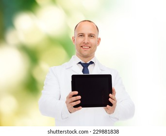 medicine, profession, advertisement and nature concept - smiling male doctor showing tablet pc computer screen over natural background
