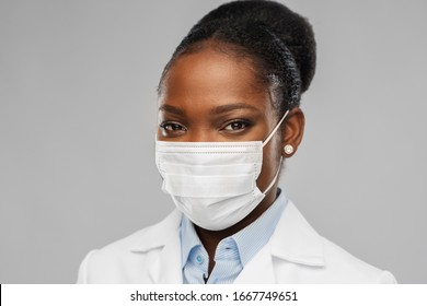 medicine, profession and healthcare concept - african american female doctor or scientist in protective facial mask over grey background
