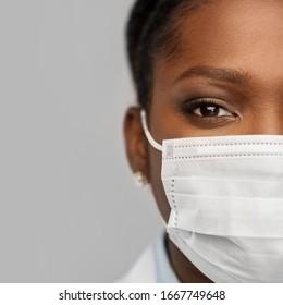 医学、専門、医療のコンセプト – グレイの背景に保護顔面を持つアフリカ系アメリカ人の女性医師または科学者の接写