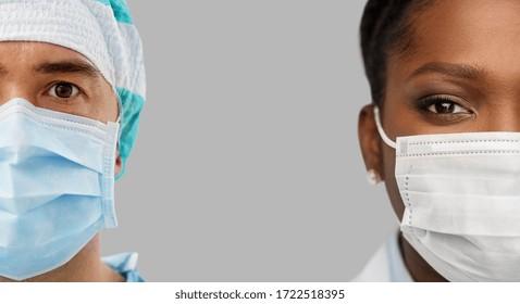 医療、専門、医療のコンセプト – グレイの背景にウイルスの病気から保護するために、顔に医療用マスクを付けたアフリカの女性とヒスパニック系の男性の医師の接写